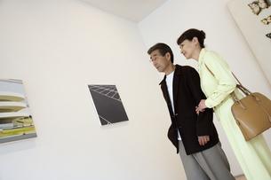 ギャラリーで鑑賞する熟年夫婦の写真素材 [FYI04051816]