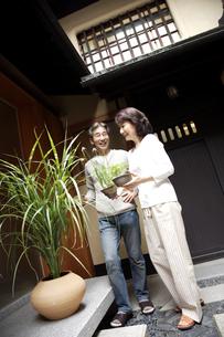 和風の鉢植えを持つ熟年夫婦の写真素材 [FYI04051821]