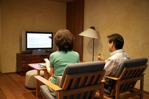 プラズマテレビを見る熟年夫婦の写真素材 [FYI04051836]
