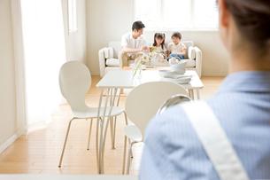 キッチンの母とリビングの父と子の写真素材 [FYI04052147]