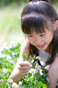 四つ葉のクローバーを持つ女の子の写真素材 [FYI04052341]