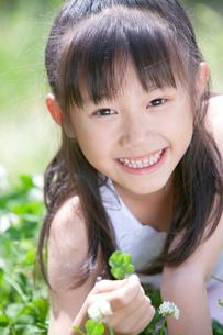 四つ葉のクローバーを持つ女の子の写真素材 [FYI04052342]