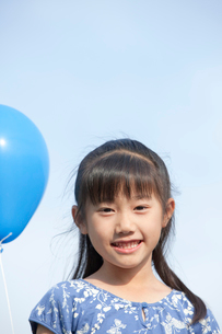 青空と風船を持つ女の子の写真素材 [FYI04052348]