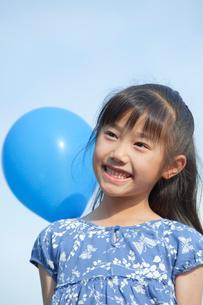 青空と風船を持つ女の子の写真素材 [FYI04052351]