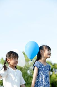 青空と風船を持つ姉妹の写真素材 [FYI04052352]