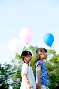 青空と風船を持つ姉妹の写真素材 [FYI04052353]