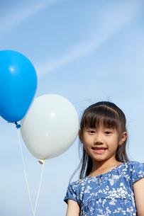 青空と風船を持つ女の子の写真素材 [FYI04052356]
