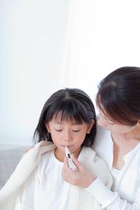 娘の熱を計る母親の写真素材 [FYI04052394]