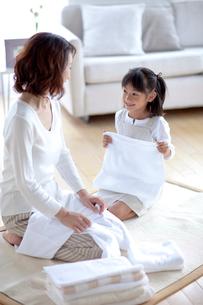 洗濯物を片づける母と娘の写真素材 [FYI04052416]