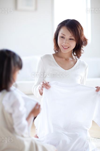 洗濯物を片づける母と娘の写真素材 [FYI04052418]