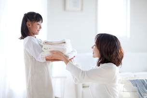 洗濯物を片づける母と娘の写真素材 [FYI04052421]