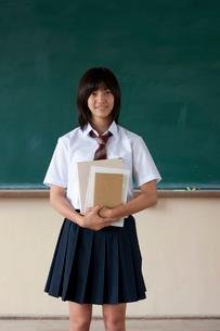 黒板の前に立つ日本人の女子高校生の写真素材 [FYI04052492]
