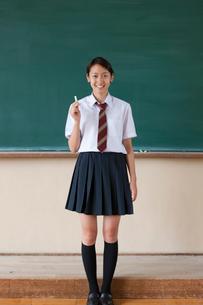 黒板の前に立つ日本人の女子高校生の写真素材 [FYI04052497]
