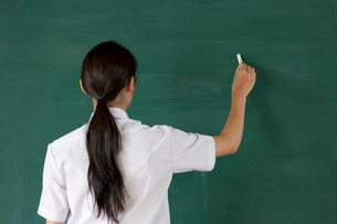 黒板に文字を書く女子高校生の写真素材 [FYI04052499]
