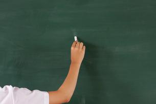 チョークで黒板に文字を書く手の写真素材 [FYI04052501]