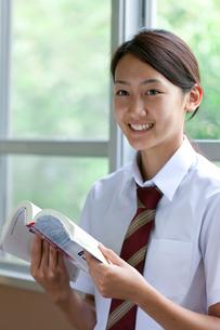 廊下で教科書を読む女子高校生の写真素材 [FYI04052507]