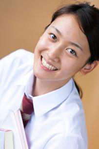 教科書を持つ笑顔の女子高校生の写真素材 [FYI04052516]