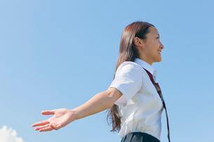 空に向かって両手を広げる女子高校生の写真素材 [FYI04052525]