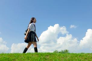 土手を歩く女子高校生の写真素材 [FYI04052526]