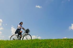 土手で自転車に乗る女子高校生の写真素材 [FYI04052532]