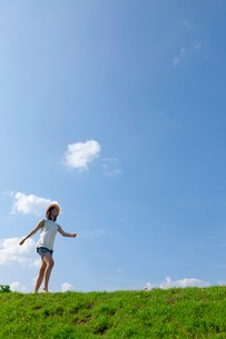 土手を歩く帽子をかぶった10代の女の子の写真素材 [FYI04052538]