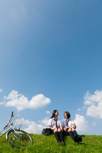 土手に座っておしゃべりする二人の女子高校生の写真素材 [FYI04052540]
