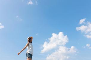 空に向かって両手を広げる帽子をかぶった10代の女の子の写真素材 [FYI04052542]