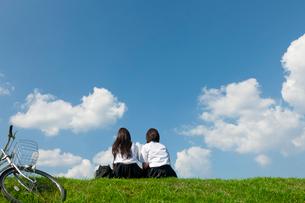 土手に座っておしゃべりする二人の女子高校生の写真素材 [FYI04052543]