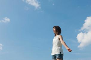 空に向かって両手を広げる10代の女の子の写真素材 [FYI04052545]