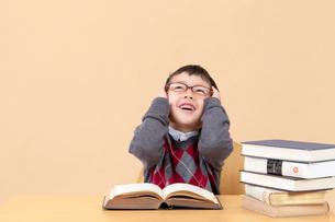 本の前で頭を抱える男の子の写真素材 [FYI04052746]