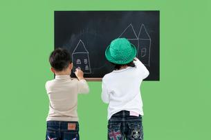 黒板に絵を描く男の子と女の子の写真素材 [FYI04052753]