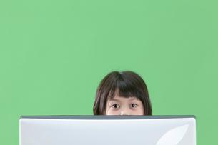 パソコンモニターの向うから覗く女の子の写真素材 [FYI04052758]