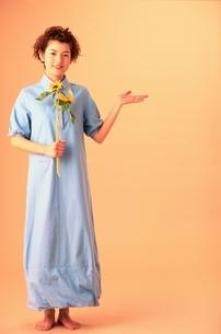 ヒマワリを持ち手を上げる日本人女性の写真素材 [FYI04053069]