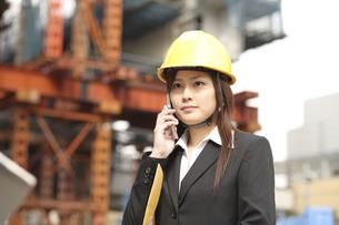建設現場で携帯を使うスーツ姿の女性の写真素材 [FYI04053471]