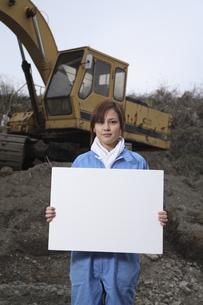 重機の前に立って白い紙を持つ女性の写真素材 [FYI04053476]
