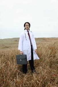 草むらに立つ日本人青年医師の写真素材 [FYI04053544]