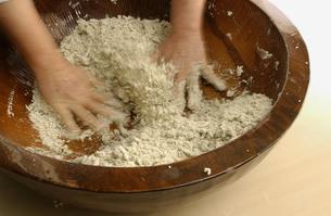 そば打ち用のそば粉を混ぜる手の写真素材 [FYI04053776]