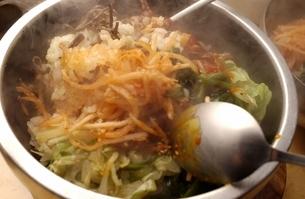 韓国料理のユッケビビンバを混ぜるの写真素材 [FYI04053799]