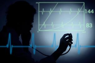 聴診器を向ける男性医師の影と心電図の写真素材 [FYI04054216]