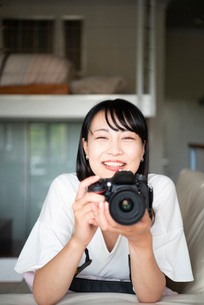 一眼レフカメラを構えて笑っている女性の写真素材 [FYI04055826]