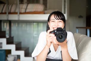 一眼レフカメラを構えて笑っている女性の写真素材 [FYI04056782]