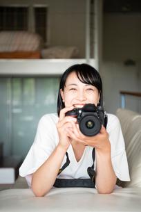 一眼レフカメラを構えて笑っている女性の写真素材 [FYI04057177]
