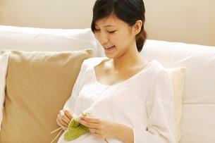 ソファで編み物をする妊婦の写真素材 [FYI04057247]