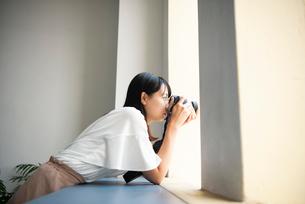 一眼レフカメラで写真を撮影している女性の写真素材 [FYI04057663]