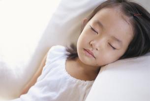 ソファーで昼寝する日本人の女の子の写真素材 [FYI04058200]