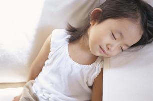 ソファーで昼寝をしながら微笑む日本人の女の子の写真素材 [FYI04058202]