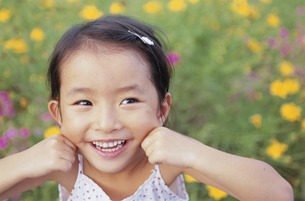 花畑に立つ笑顔の女の子の写真素材 [FYI04058287]