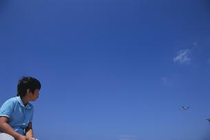 飛行機を見つめる男の子の写真素材 [FYI04058298]