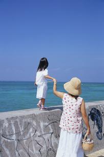 防波堤を歩くお母さんと女の子の写真素材 [FYI04058299]