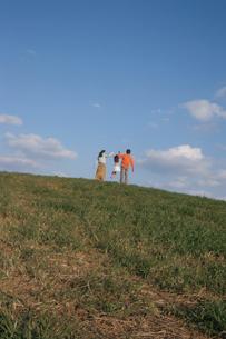 手をつなぎ丘を歩く親子3人の後姿の写真素材 [FYI04058319]